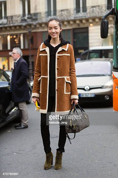 Model Fei Fei sun exits the Stella McCartney show in an Anna sui coat and Tory Burch purse on Day 7 of Paris Fashion Week FW15 on March 9 2015 in...