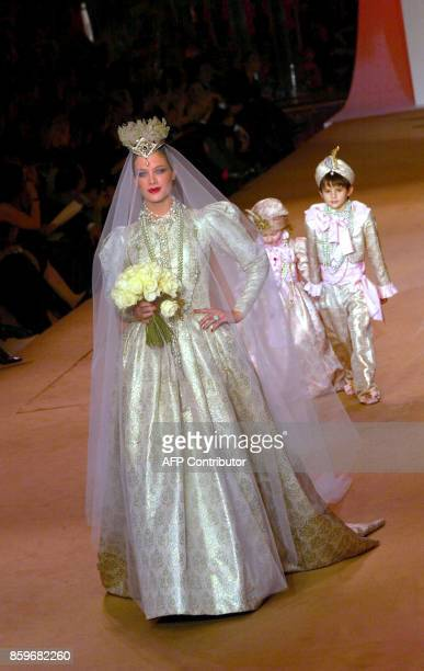 A model followed by children presents a wedding dress by French designer Yves Saint Laurent 22 January 2002 during the retrospective part of Saint...