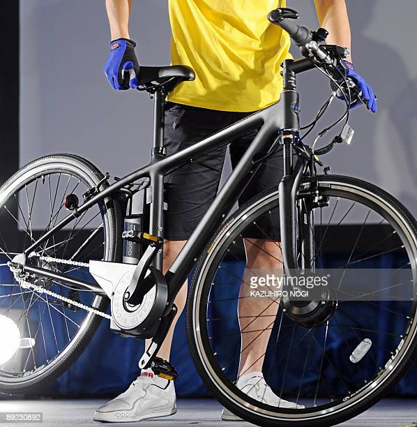 A model for Japan's Sanyo Electric co displays one of the company's new models of electric hybrid bicycles the 'eneloop bike CYSPK227' during a press...