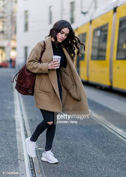 Model Frankie Miles wearing a brown wool coat from Subdued navy top and ripped denim jeans and white Adidas sneaker on March 24 2016 in Berlin Germany