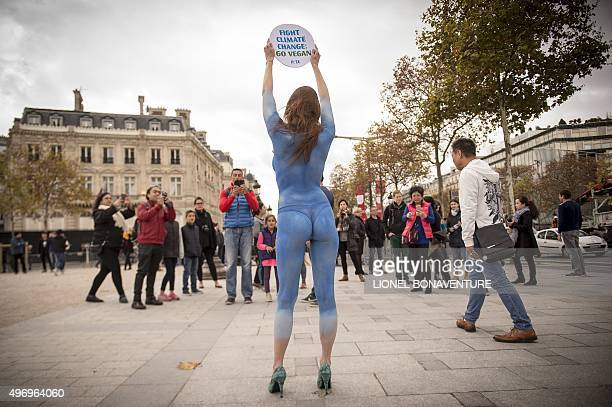 A model from PETA with a world map painted on her body poses in front of the Arc de Triomphe in Paris on November 13 2015 with a sign reading 'Fight...