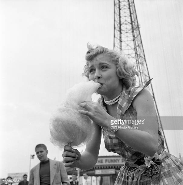 Model from the CBS gameshow 'The Big Payoff' Cindy Robbins with cotton candy at Steeplechase Park Coney Island Brooklyn NY Image dated May 11 1953
