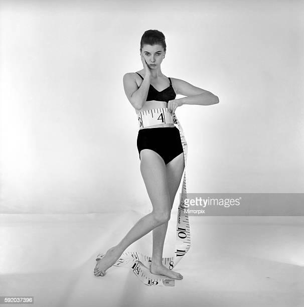 Model Gay Protheroe with outsize tapemeasure December 1956