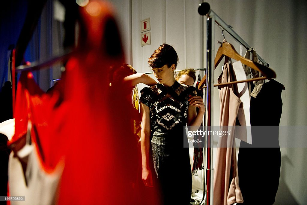 A model gets dressed backstage before the Black Coffee show at SA Fashion Week at the Crowne Plaza on April 12, 2013, in Johannesburg, South Africa.