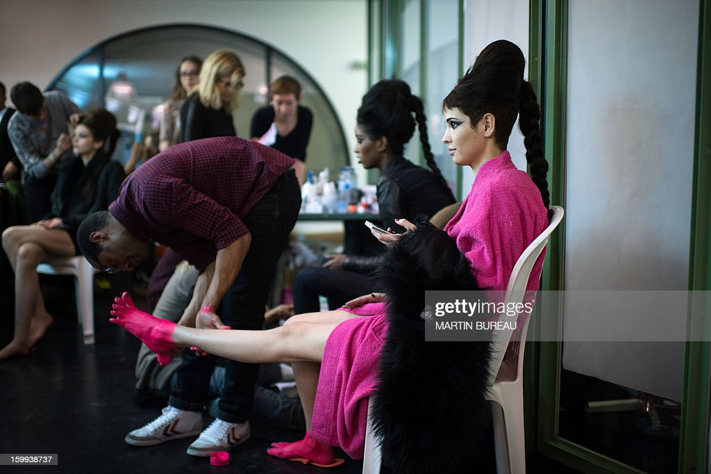 A model gets her feet painted backstage ahead of French designer Jean Paul Gaultier's show during the Haute Couture Spring-Summer 2013 collection presentations on January 23, 2013 in Paris.