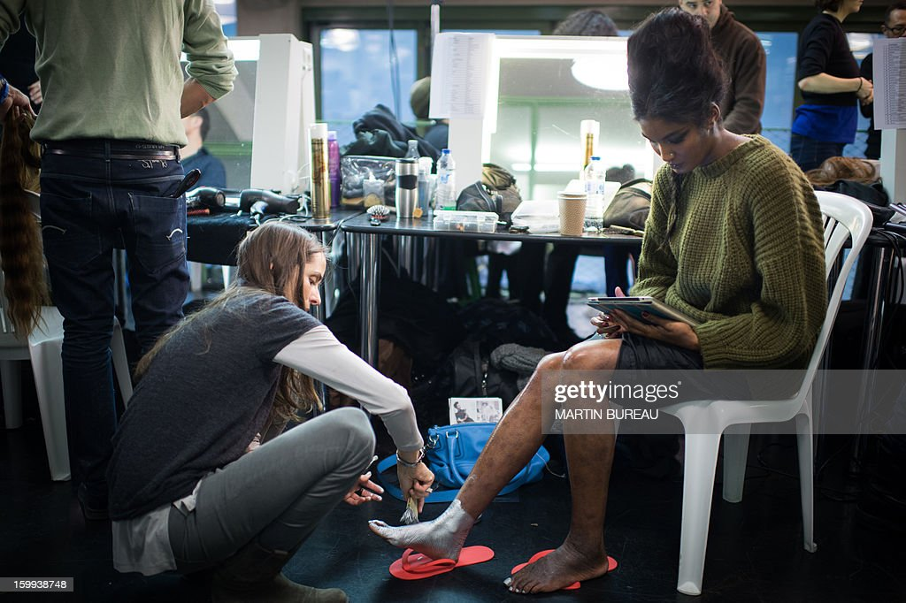A model gets her feet painted backstage ahead of French designer Jean Paul Gaultier's show during the Haute Couture Spring-Summer 2013 collection presentations on January 23, 2013 in Paris. AFP PHOTO / MARTIN BUREAU