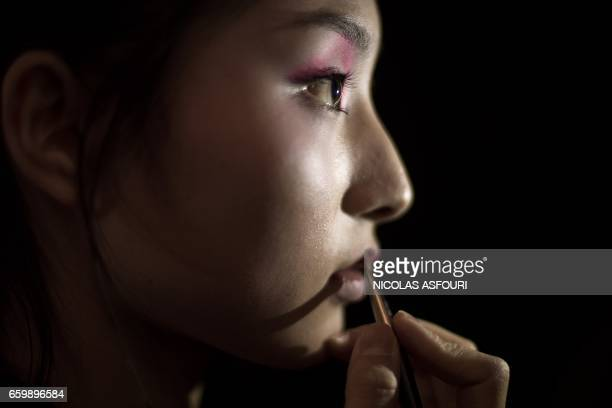 TOPSHOT A model gets her make up done backstage before parading the Chenwen studio collection by Chen Wen during China Fashion Week in Beijing on...