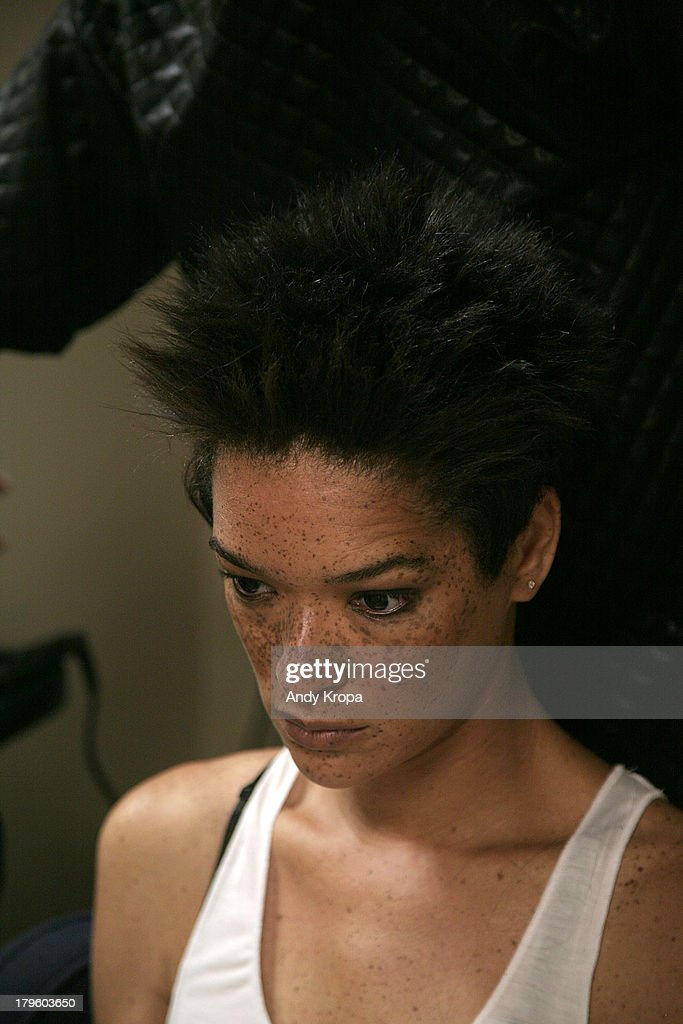 A model gets makeup applied before the Ebony White presentation during Mercedes-Benz Fashion Week on September 5, 2013 in New York City.