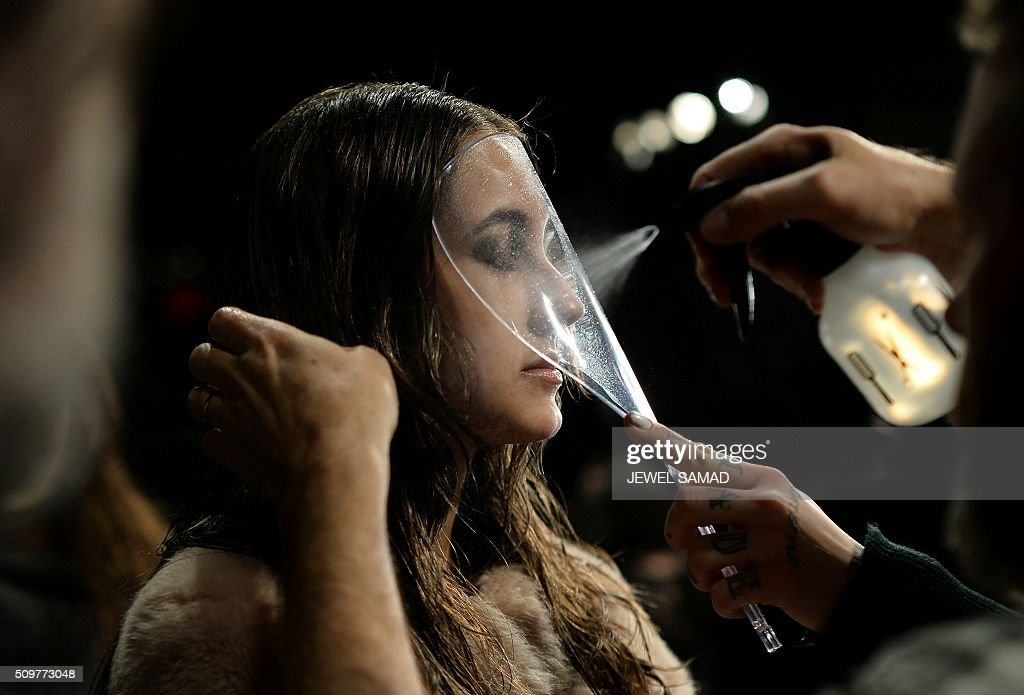 A model gets ready backstage to present Tadashi Shoji designs during the Fall 2016 New York Fashion Week at the Arcat Moynihan Station on February 12, 2016, in New York. / AFP / JEWEL SAMAD