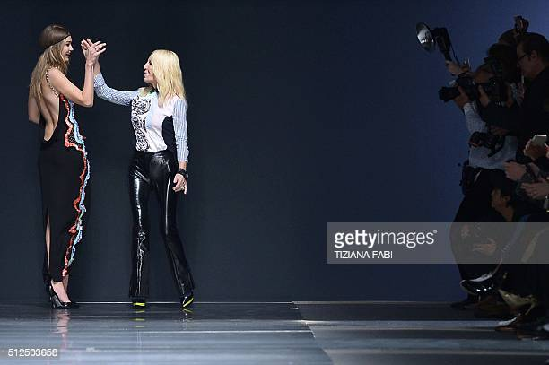 Model Gigi Hadid and designer Donatella Versace shake hands at the end of the show for fashion house Versace as part of the Women Autumn / Winter...