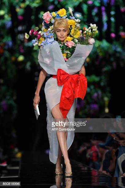 Model Gigi Hadid presents a creation for fashion house Moschino during the Women's Spring/Summer 2018 fashion shows in Milan on September 21 2017 /...