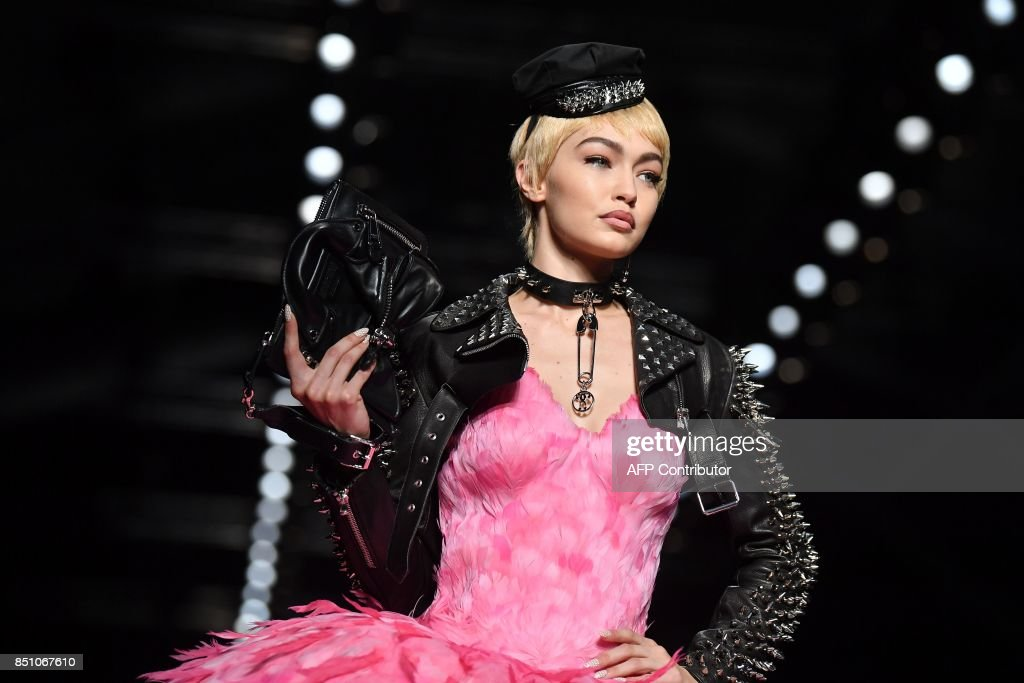 Model Gigi Hadid presents a creation for fashion house Moschino during the Women's Spring/Summer 2018 fashion shows in Milan, on September 21, 2017. / AFP PHOTO / Marco BERTORELLO