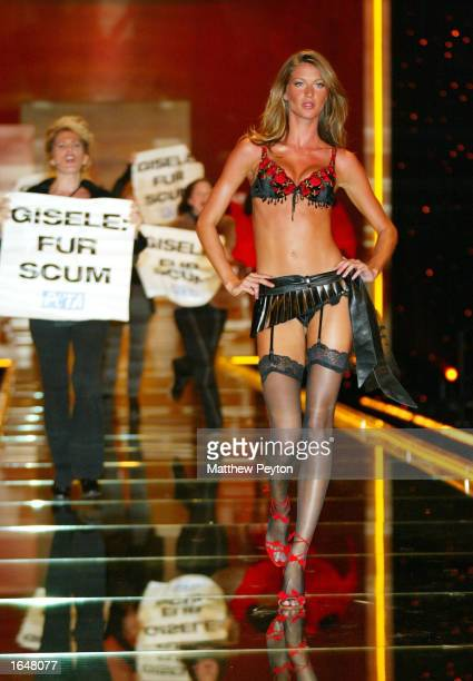Model Gisele Bundchen walks the runway while activists for the PETA People for the Ethical Treatment of Animals protest at the Victoria Secret...