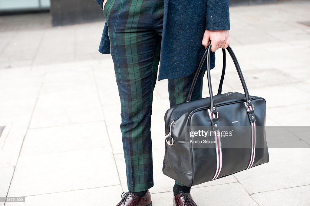 Model Harrison Tea wears a Vivienne Westwood suit, Russell and Bromley shoes, Ben Sherman bag and a Peter Werth coat day 3 of London Mens Fashion Week Autumn/Winter 2014, on January 08, 2014 in London, England.