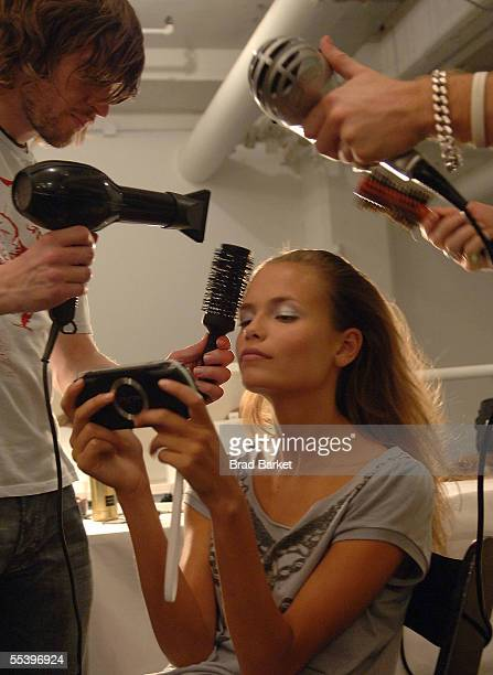 A model has her hair done while playing a portable video game backstage at the Narciso Rodriguez Spring 2006 fashion show during Olympus Fashion Week...