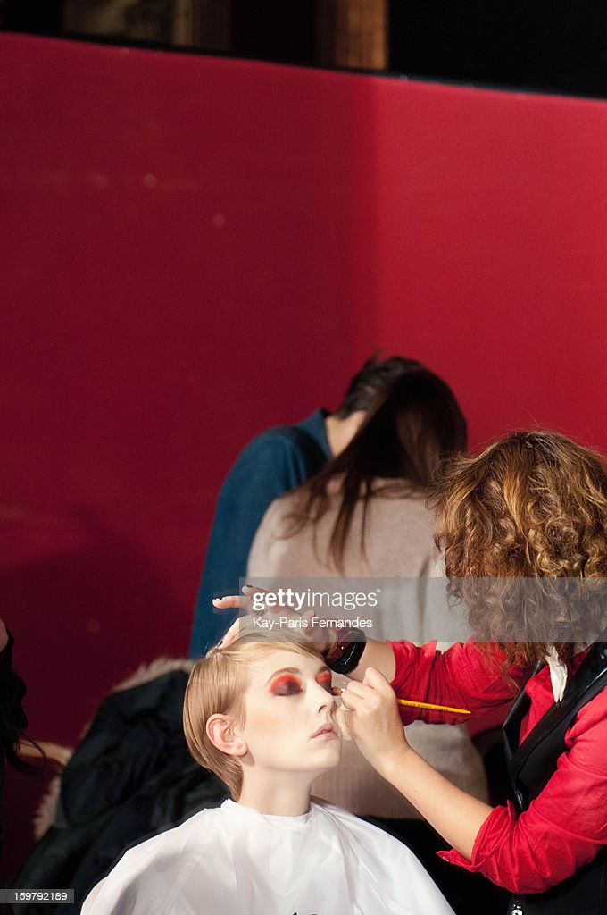 A model has her make-up done backstage during the Rynshu Men Autumn / Winter 2013 show as part of Paris Fashion Week on January 20, 2013 in Paris, France.