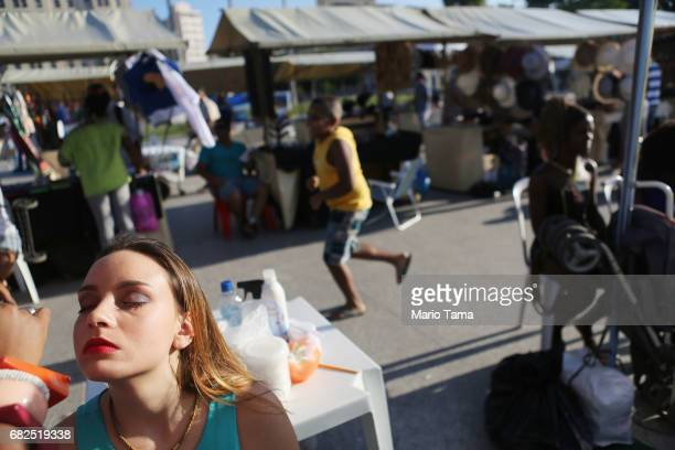 A model has makeup applied as she prepares to perform in a fashion show on May 12 2017 in Rio de Janeiro Brazil Today marked one year since President...