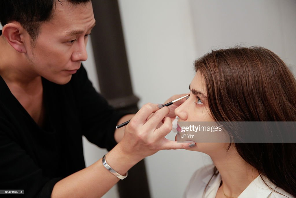 A model has makeup applied backstage at the Naeem Khan Fall/Winter 2014 Bridal Collection presentation and reception on October 12, 2013 in New York City.