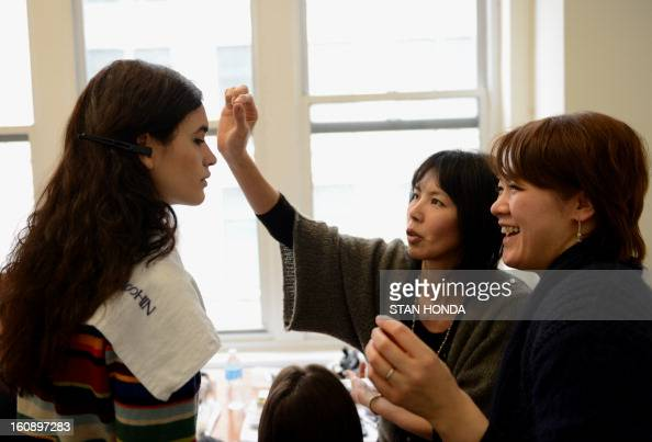 A model has makeup applied backstage before the 4 Corners of a Circle show during the MercedesBenz Fashion Week Fall 2013 collections on February 7...