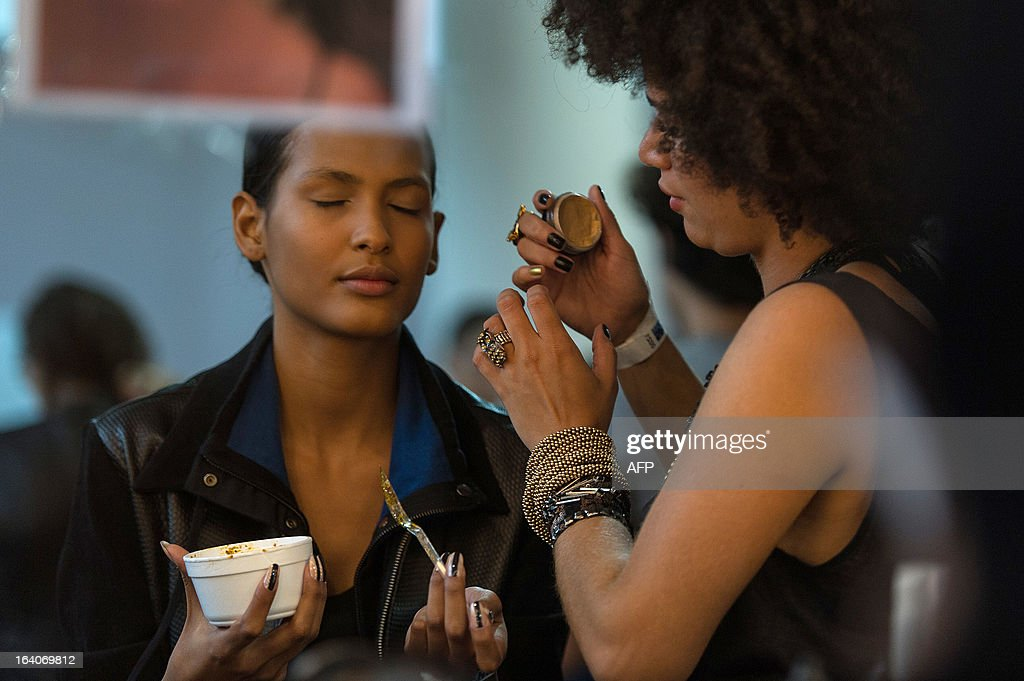 A model has make-up applied before presenting a creation by Acquastudio for Esther Bauman during the 2013 Summer collections of the Sao Paulo Fashion Week in Sao Paulo, Brazil, on March 19, 2013. AFP PHOTO / Yasuyoshi CHIBA
