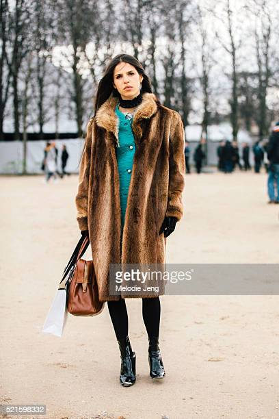 Model Hayett McCarthy wears a long brown fur coat a teal jacket a brown bag and latex black boots after the Carven show at the Tuileries on Day 3 of...