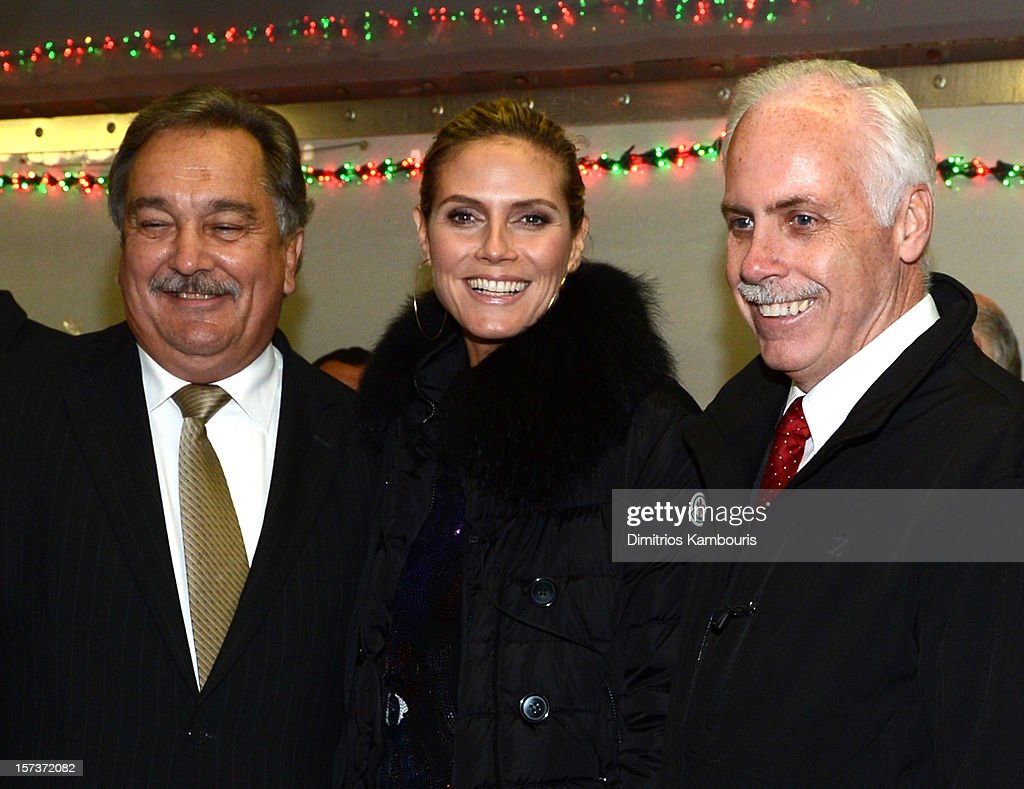 Model Heidi Klum (C) poses for a photograph with Village of Lindenhurst Mayor Thomas A. Brennan (L) and Deputy Mayor Kevin McCaffrey (R) during a tree lighting ceremony as they team up with friends at AOL, Patch and The American Red Cross to benefit Hurricane Sandy relief efforts at American Red Cross and Patch Sites on December 2, 2012 in Lindenhurst, New York.