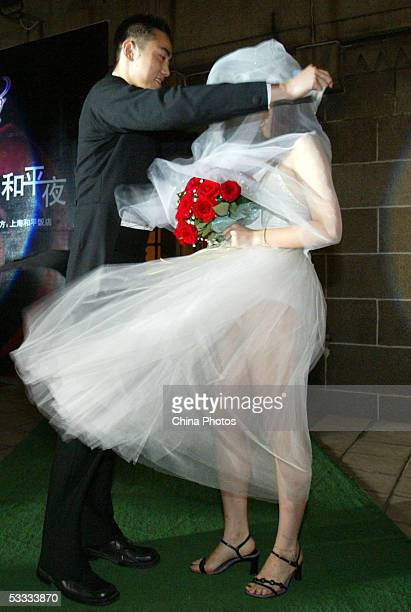 A model helps his partner fix her wedding shawl in heavy wind during a wedding dress show on the top of the Peace Hotel on August 6 2005 in Shanghai...