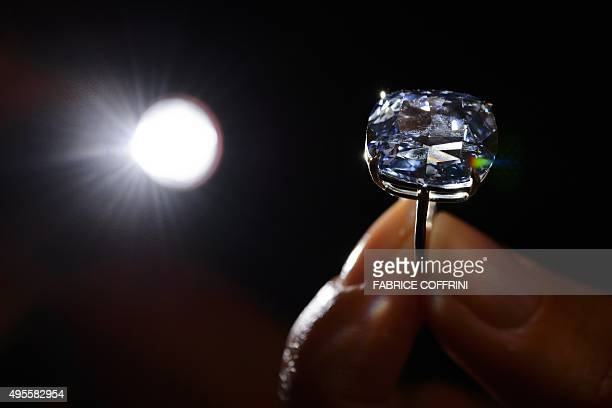 A model holds a 1203carat blue diamond during a press preview by auction house Sotheby's in Geneva on November 4 2015 A 1203carat blue diamond could...