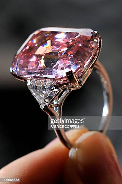 A model holds a 2478 carat fancy intense pink diamond during a Sotheby's auction preview on November 10 2010 in Geneva The rare diamond mounted on a...