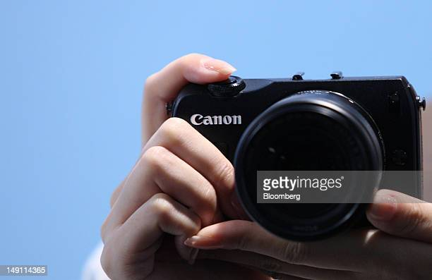 A model holds a Canon Inc EOS M mirrorless interchangeablelens camera at its unveiling in Tokyo Japan on Monday July 23 2012 Canon Inc the world's...