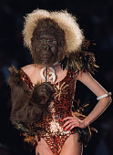 A model holds a gorilla mask and glove as she presents a sprangled body by British designer John Galliano 08 July 2000 for the Christian Dior...