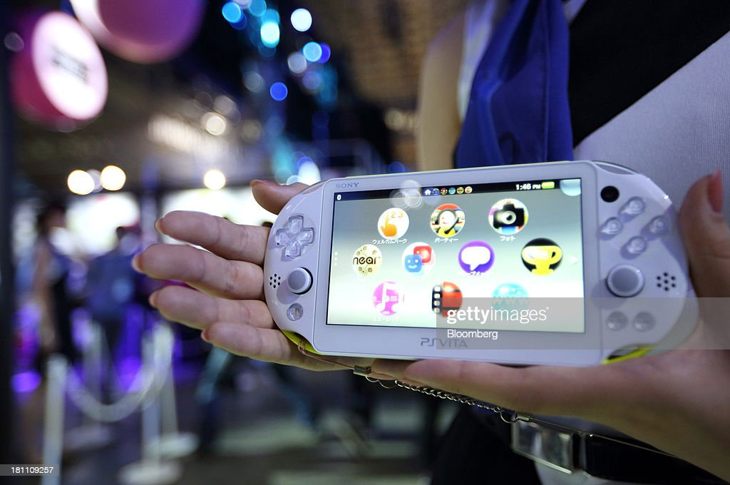 A model holds a Sony Computer Entertainment Inc. PlayStation Vita (PS Vita) portable video game player at the Tokyo Game Show 2013 in Chiba, Japan, on Thursday, Sept. 19, 2013. The Tokyo Game Show runs till Sept. 22. Photographer: Tomohiro Ohsumi/Bloomberg via Getty Images