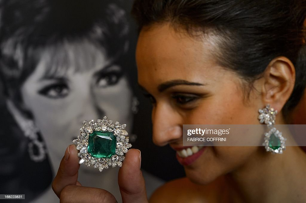 A model holds an emerald and diamond brooch (estimate CHF 145'000-190'000, USD 150'000-200'000) and wears a pair of diamond earclips by Bulgari, 1964 (estimate CHF 145'000-240'000, USD 150'000-250'000) next to a picture of Italian actress Gina Lollobrigida during a press preview of auction house Sotheby's on May 7, 2013 in Geneva. Lollobrigida is to sell some of her jewellery in Geneva on May 14, 2013 with part of the proceeds going to help stem cell research, auction house Sotheby's said. Designed by Italian creator Bulgari in the 1950s and 1960s, the items include pearl and diamond earrings and a 19.3-carat diamond ring. Both pieces are valued at between $600,000 and one million dollars (465,000 - 775,000 euros). The 85-year-old star of 'The World's Most Beautiful Woman' and 'Come September,' one of Italy's best-known actresses, says she wants to devote herself to sculpture and 'a sculptor doesn't need jewellery', the Sotheby's statement said.