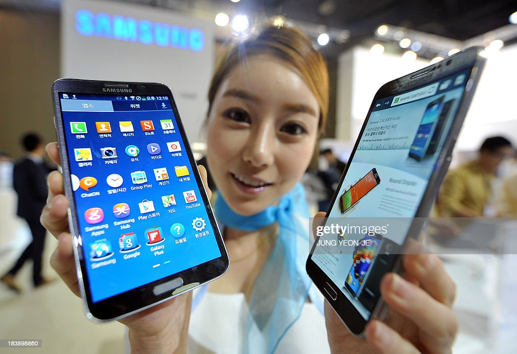 A model holds Samsung's first 'curved' smartphone Galaxy Round, a 5.7-inch handset with a display that is slightly rounded on both sides, at the Electronics and IT Industry Fair in Goyang, north of Seoul, on October 10, 2013. Samsung's first smartphone with a curved display screen enters the South Korean market on October 10, as the electronics giant seeks to maintain its lead in the increasingly saturated market. AFP PHOTO / JUNG YEON-JE