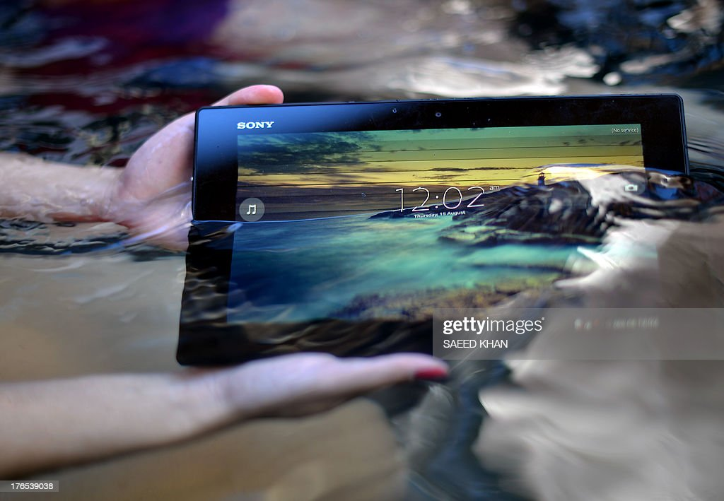 A model holds Sony's latest waterproof tablet while operating it under water in the central business district of Sydney on August 15, 2013. Sony has introduced its latest waterproof technology, the Xperia Tablet Z, that can work a meter deep in water. AFP PHOTO / Saeed KHAN
