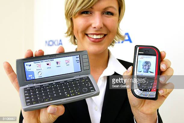 A model holds the new Nokia 7610 mobile phone and the Communicator 9500 at the CeBIT technology trade fair March 18 2004 in Hanover Germany This year...