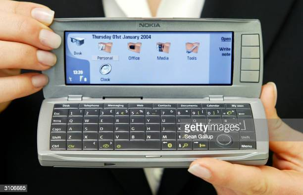A model holds the new Nokia Communicator 9500 mobile phone at the CeBIT technology trade fair March 18 2004 in Hanover Germany The 9500 is wifi or...
