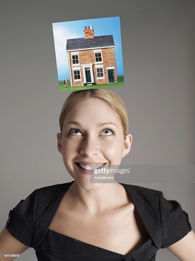 Model home on top of young woman's head representing homeownership : Stock Photo
