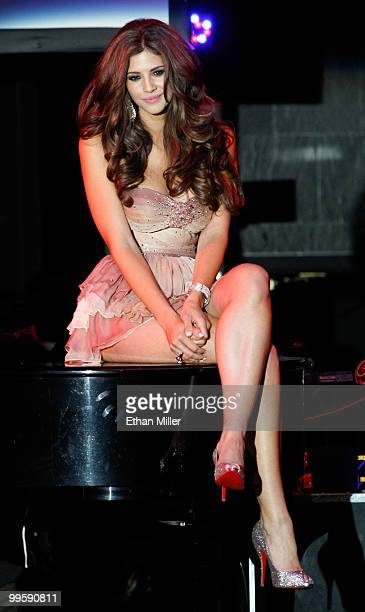Model Hope Dworaczyk sits on a piano during a performance by singer Robin Thicke at a party introducing her as the 2010 Playboy Playmate of the Year...