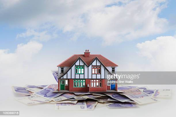 Model house on a stack of twenty pound notes
