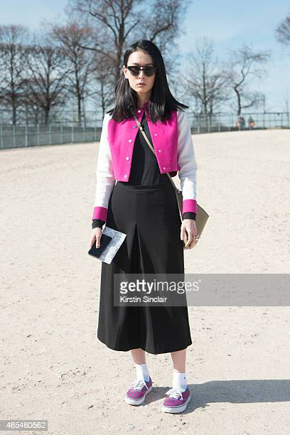 Model Hsin Yu wears Komono sunglasses Shiatzy Chen jacket Vans shoes Cos culottes and Celine bag on day 4 of Paris Collections Women on March 06 2015...