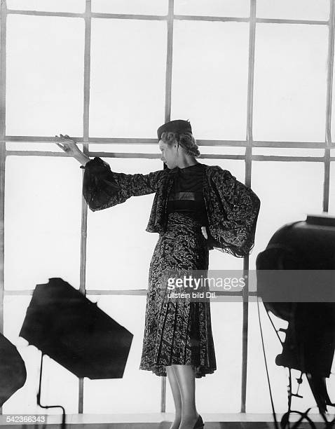 Model im Kostüm mit Hut kurze Jacke mit weiten Ärmeln Rock mit Falten beides im floralen Design veroeffentlicht 'Dame' 12/1937 1937 Aufnahme Imre v...