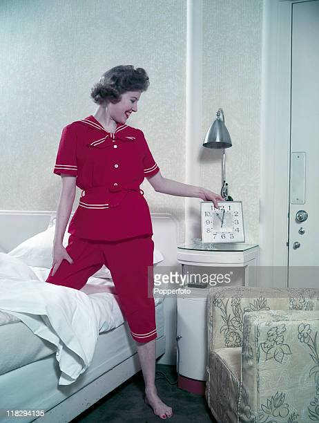 A model in a twopiece red nautically inspired sleepwear ensemble with white piping checks her clock before going to bed circa 1955