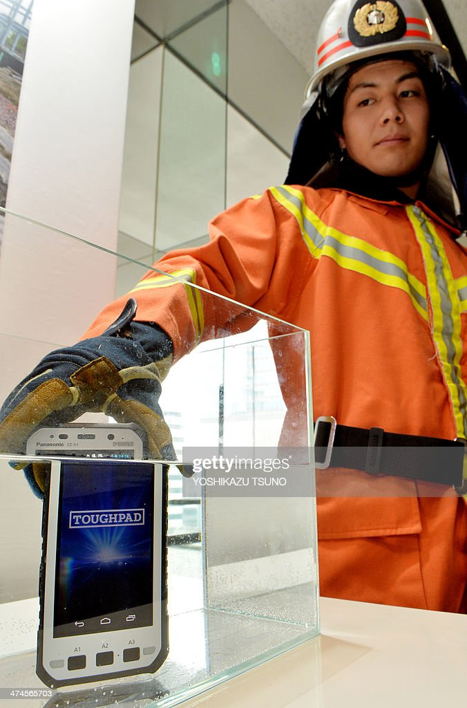 A model in fireman's gear demonstrates a water proof test on the new heavy duty tablet computer of Japanese electronics giant Panasonic 'Toughpad FZ-X1', equipped with 5-inch touch-pad LCD display with long-life battery in Tokyo on February 24, 2014. The new Toughpad with fully water, dust, shock and vibration-resistant body, will go on sale in Japan in June. AFP PHOTO/Yoshikazu TSUNO