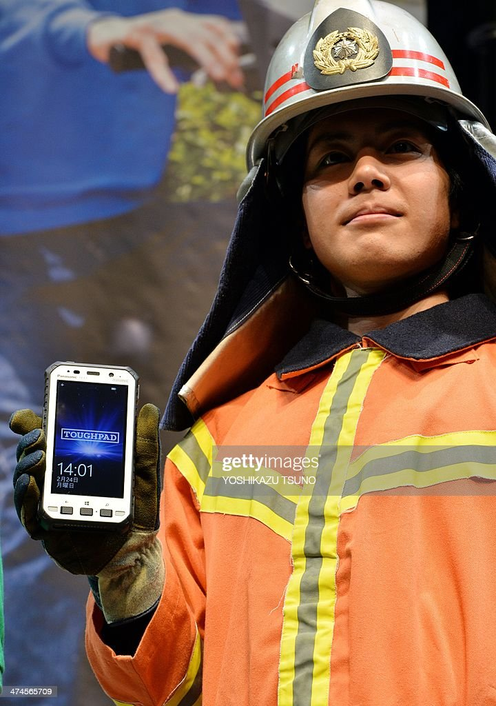 A model in fireman's gear displays the new heavy duty tablet computer of Japanese electronics giant Panasonic 'Toughpad FZ-X1', equipped with 5-inch touch-pad LCD display with long-life battery in Tokyo on February 24, 2014. The new Toughpad with fully water, dust, shock and vibration-resistant body, will go on sale in Japan in June. AFP PHOTO/Yoshikazu TSUNO