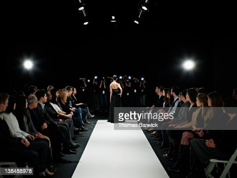 Model in gown at end of catwalk posing