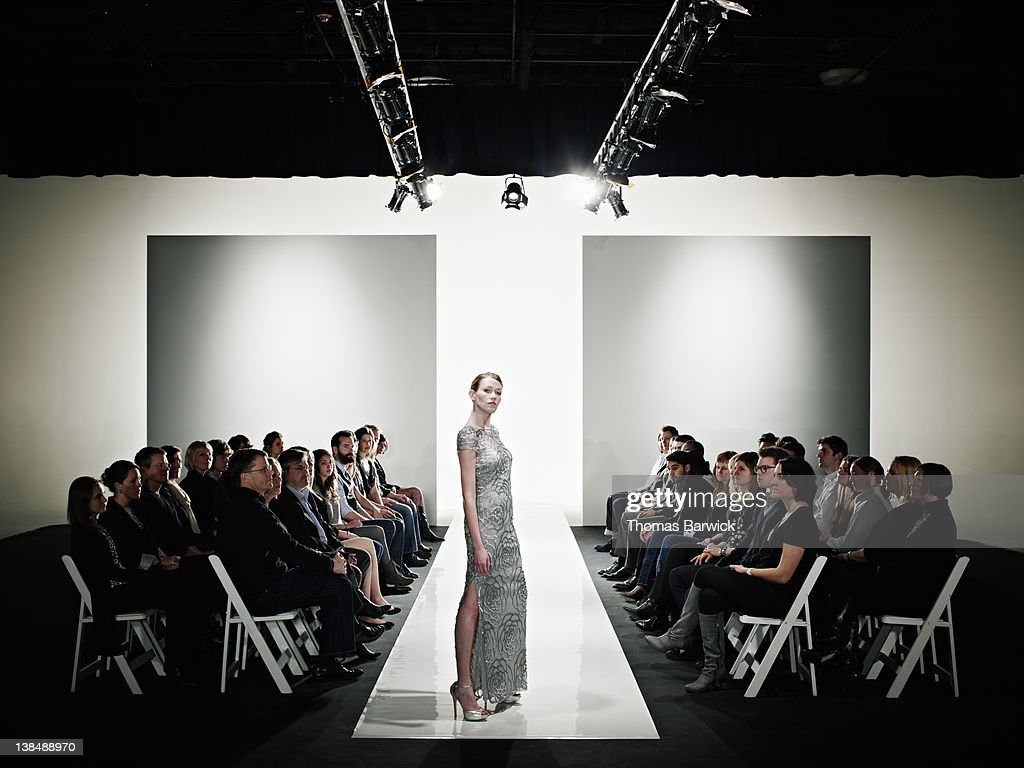 Model in gown posing at end of catwalk : Stock Photo
