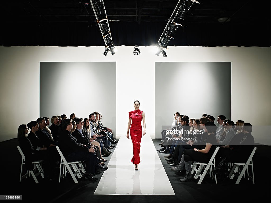 Model in gown walking down catwalk at fashion show : Stock Photo