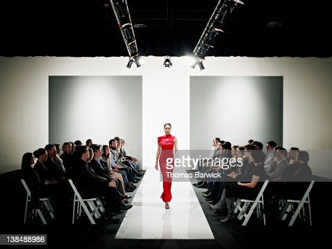 Model in gown walking down catwalk at fashion show