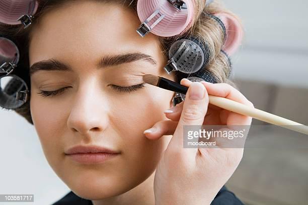 Model in Hair Curlers Having Makeup Applied